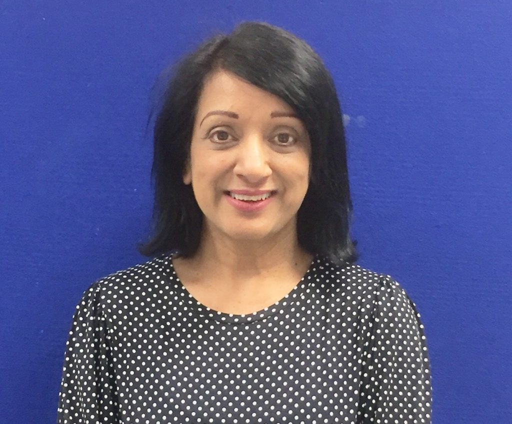 Photo of Slinda Photay who has taken part in mentoring schemes both as a mentor and mentee. She is asian with short black hair up to her shoulders. She is wearing a black blouse with white dots all over it and is standing infront of a dark blue background