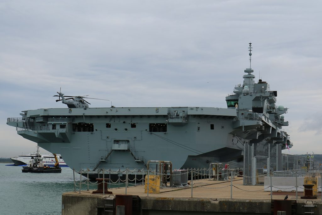 An image of HMS Queen Elizabeth, looking towards the stern, taken from a jetty and showing the ship alongside another jetty.
