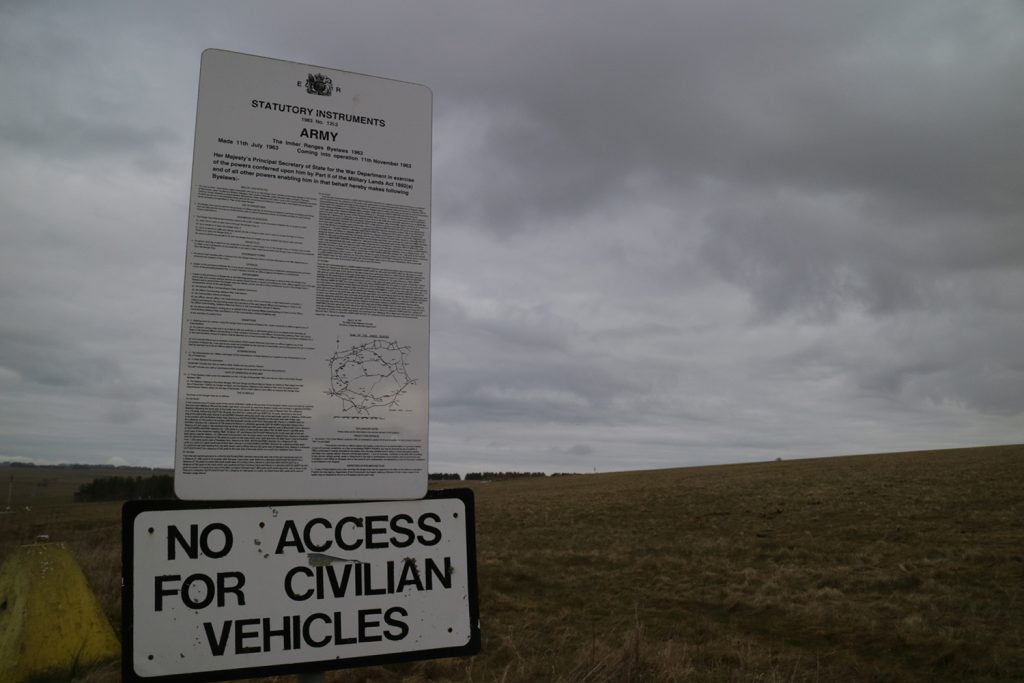 "Image of a vertical sign, with densely written text of byelaws. Under that is another sign which says ""No access for civilian vehicles"" and behind both is a grassy landscape."