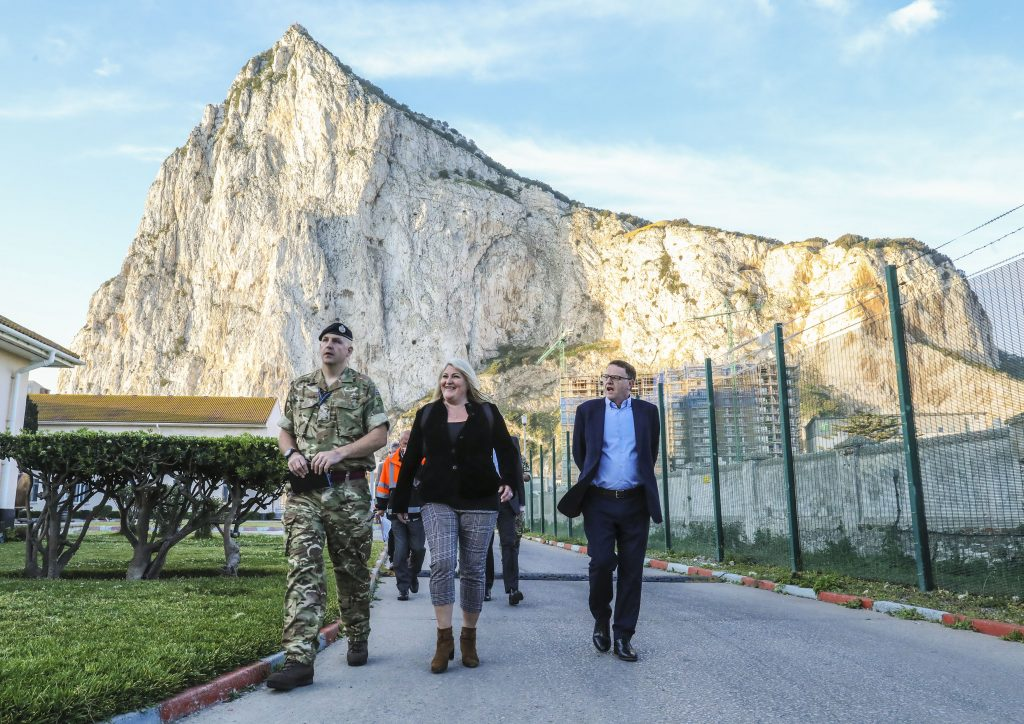 Jacqui Rock is walking alongside a soldier in uniform and a man in a suit. Behind her is the Gibraltar rock.