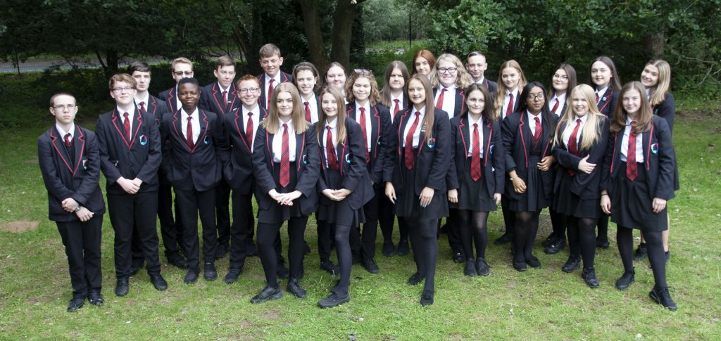 Pictured are several students from Mildenhall College Academy. They are all dressed in black blazers and trousers, a striped red and black tie and white shirts