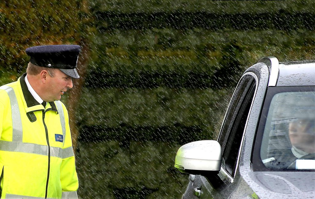 An MGS guard stands in the rain, talking to a visitor through a car window.