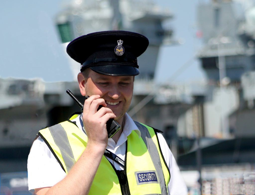 An MGS guard in uniform at Portsmouth naval base, using his walkie-talkie and with an aircraft carrier behind him.