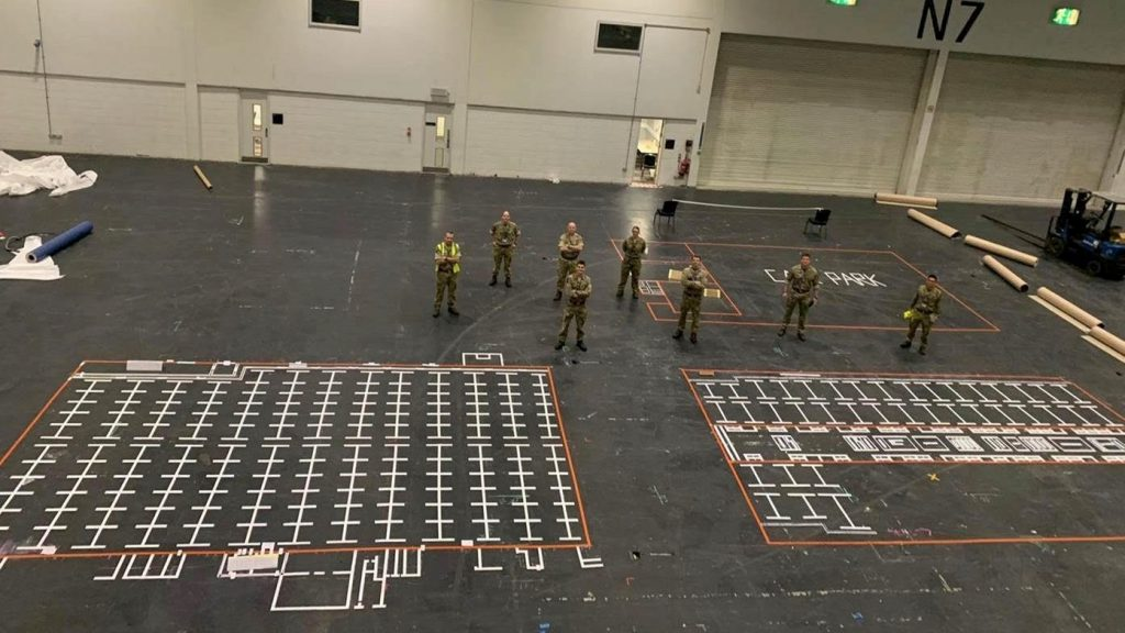 A mock up plan on the black floor drawn in white and red shows how the Nightingale Hospital may look. There is a box with a red outline and inside are lines with white marks and sections for where beds will go. There are some reservists standing near it looking at the plan.