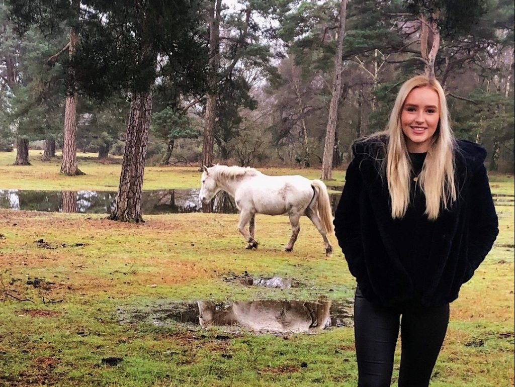 Picture of Rebecca in a black fur coat and jeans. She has blonde hair and is standing in a woodlands with a white horse behind her.