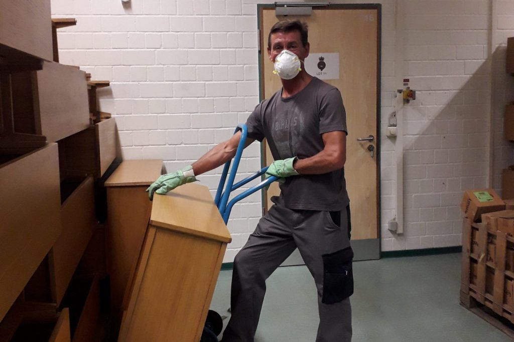 A man wearing gloves and a white face mask is moving a piece of furniture onto a blue trolley.