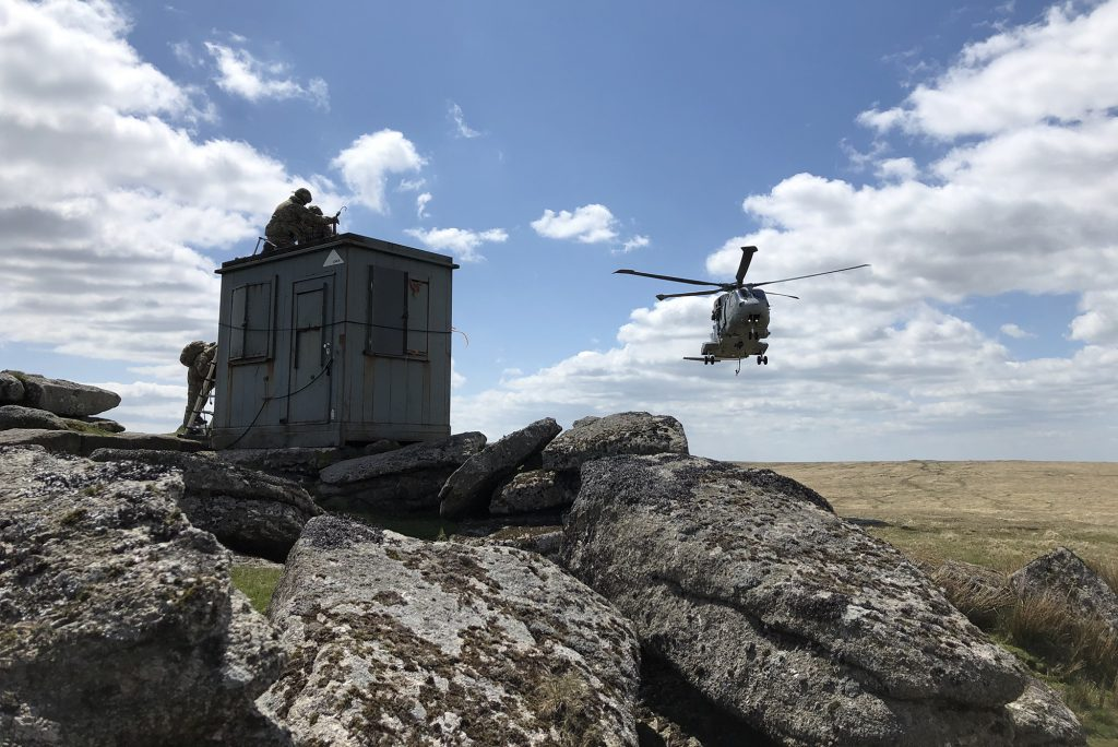 A Range Clearance hut sits on a rocky outcrop with a helicopter approaching from the rear.