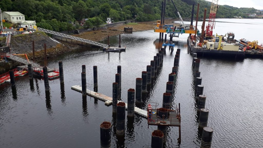 Pictured are a number of vertical brown cylinder piles that have been placed into the seabed. Pictured on the left is a white building with a silver bridge leading down to a boat.