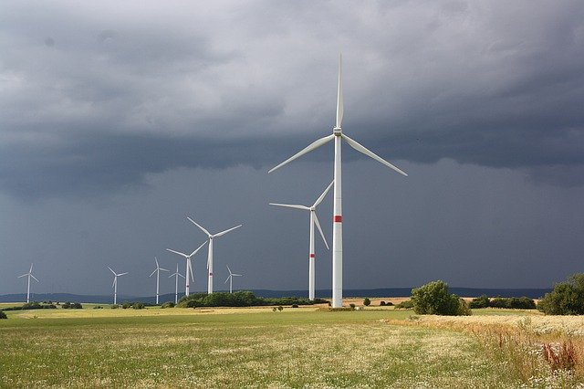Pictured is 9 wind turbines behind each other on a field. The sky is cloudy.