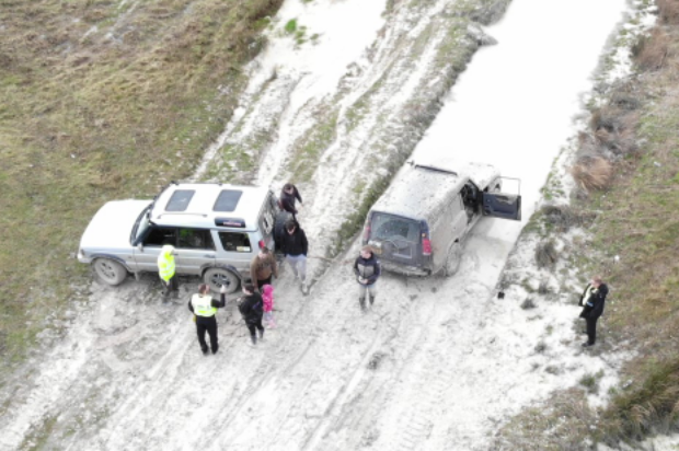An aerial view from the drone of MOD Police officers talking to the drivers of two parked 4x4 vehicles.