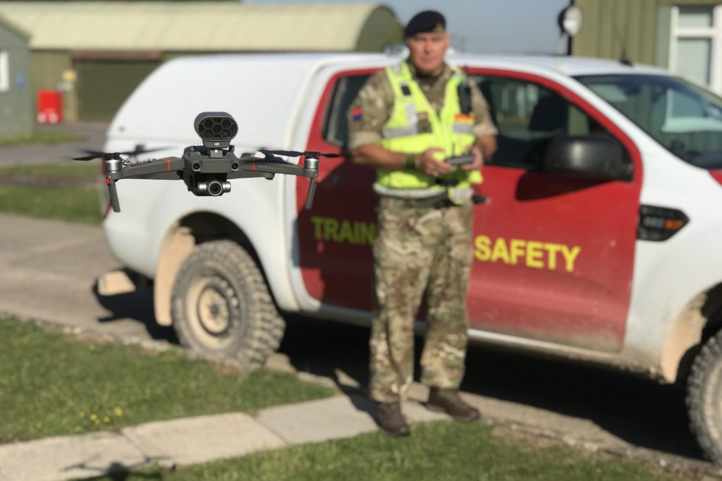 A Training Safety Marshal, wearing camoflage uniform and a high-vis vest, stands in front of a vehicle marked Training Safety. In his hands he holds a controller and near to the camera is a drone, with horizontal propellers on either side. The drone is in focus with the Training Safety Marshal, vehicle and background slightly out of focus.