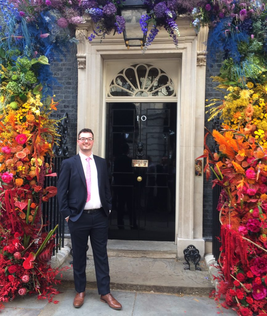Nathan is standing outside of Number 10 Downing Street which has flowers all around the doorway. The flowers are in the pride colours of red, yellow, green, blue, purple. Nathan is wearing a black suit with a white shirt and pink tie and is in smart brown shoes.