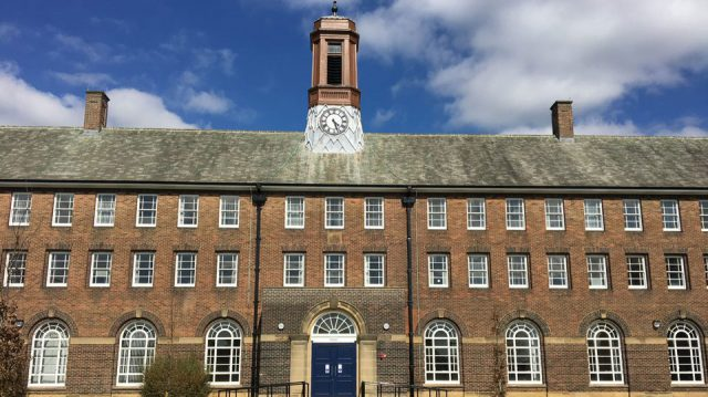 The Sandhurst Block is a grade II historic building with an old brown brick look and clock with roman numerals in the middle of it. It was refurbished to represent a modern look inside but keep the historic features of the building.