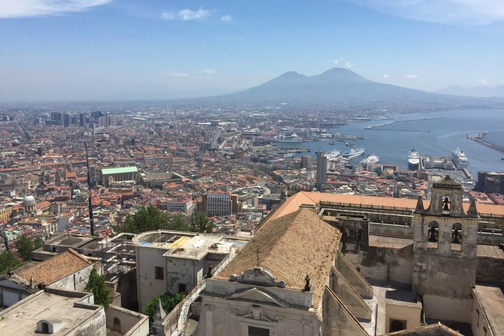 A view of Naples from a high point, with the rooftop of what appears to be a church in the foreground. Spread out behind are the rooftops of the city and to the right, the Bay of Naples with a number of cruise ships. In the distance is Mt Vesuvius.