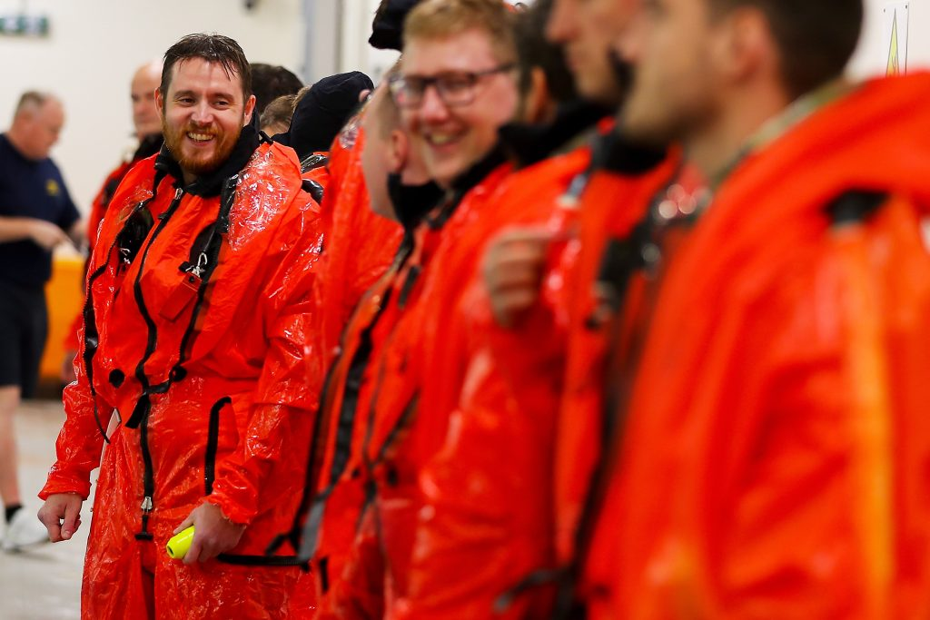 A line of sailors in bright orange dry suits. Only one is in focus, smiling at a companion next to him. His dry suit is wet.