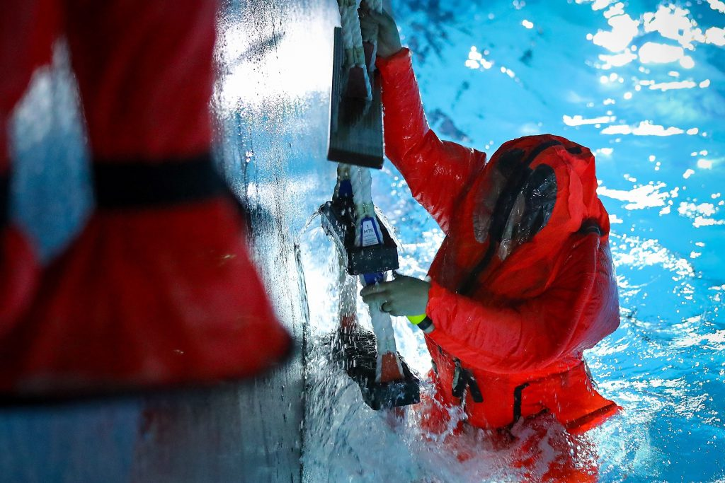 The left side of the image is a vertical wall. The right is a pool, with a sailor in an orange dry suit who is mostly in the water, but hanging on to a rope ladder with his hands.