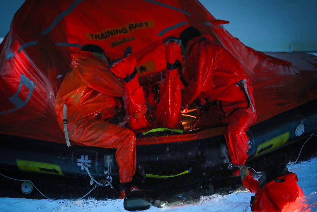 Two sailors in orange dry suits sit on the edge of an orange and black training life raft in a pool.