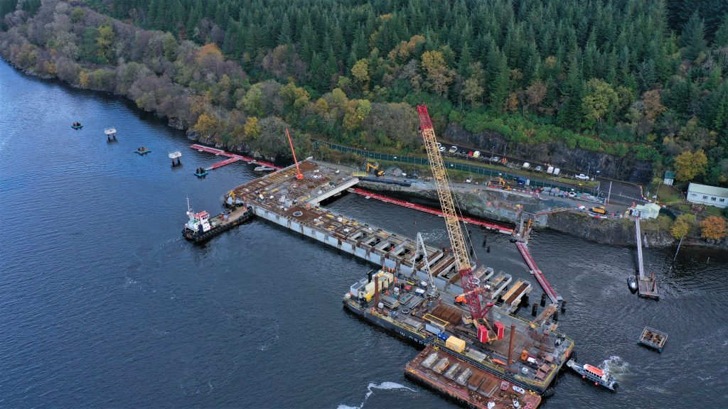 A drone image of the Northern Ammunition Jetty over the Loch Lomand sea. A big yellow and red crane is on the jetty along with a small white boat beside it. There is a road and lots of green trees on the right of the jetty.