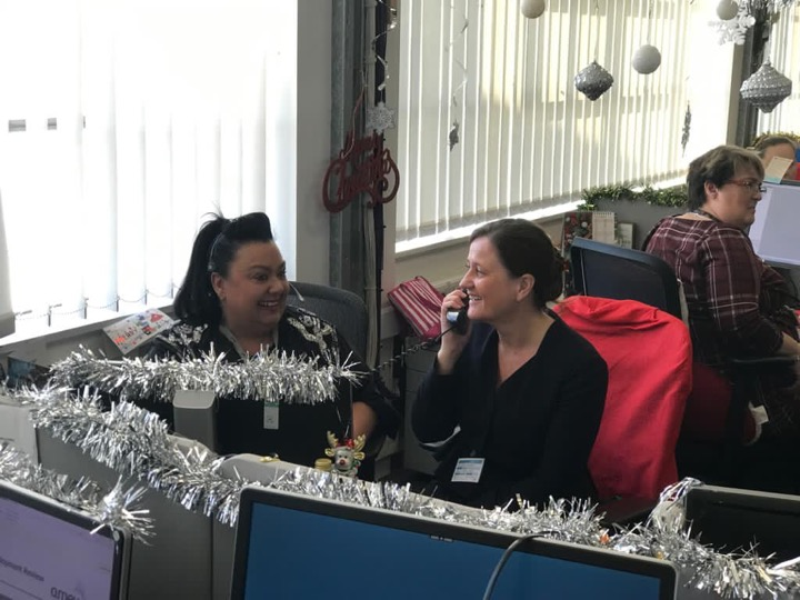 Wendy sits at a desk on the phone. She is smiling at a woman sitting next to her. Behind them is another woman, also sat at a computer. The office has tinsel and Christmas decorations.