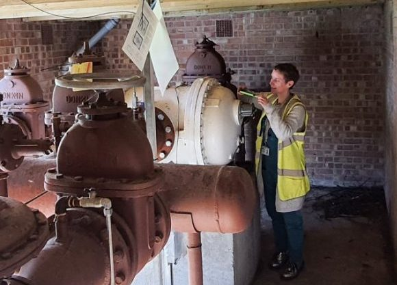 Charlie is wearing a yellow sleeveless vis-me jacket and is taking a gas meter reading with a small device. She is pictured next to a big white pipe and a brown one.