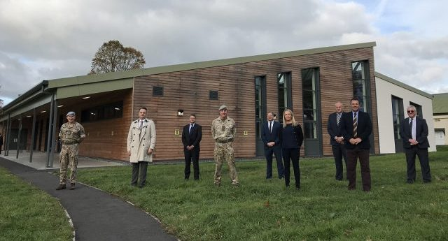 9 representatives from DIO, Landmarc and Pave aways are stood on grass infront of the new facility which is a brown woooded building with long window panels and green roofing.