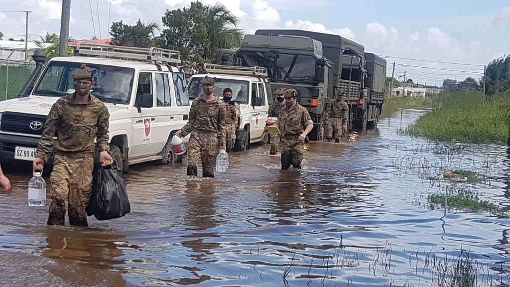 Six soldiers are walking through flooding with water cartons and bags. Next to them are white vehicles and a military truck.