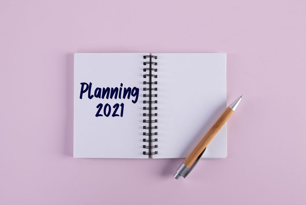 "A notebook lies open. On the left hand page it reads ""Planning 2021"". The right hand page is blank but has a pen resting on it. The background is pink."