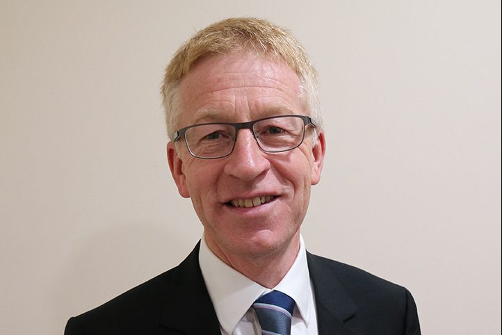 Graham Dalton, DIO's Chief Executive. Graham is a white man with light hair and glasses, wearing a black suit, white shirt and striped tie. He is smiling.