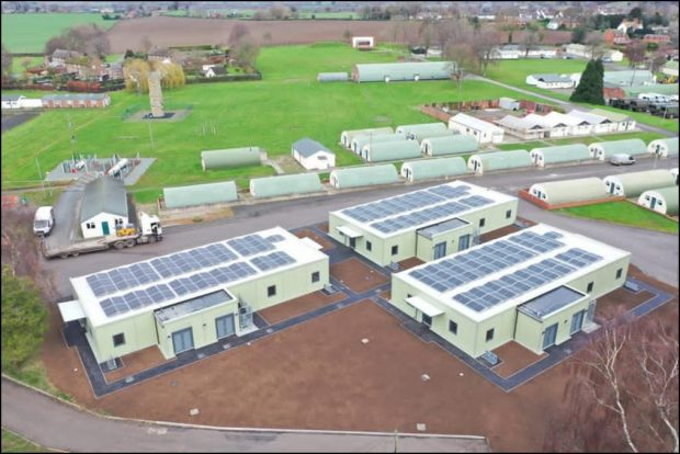 Aerial view of Nesscliffe Training Camp. In the foreground is an area of bare earth with three single storey buildings with solar panels on their roofs. In the background are multiple Nissen huts and a large area of grass.