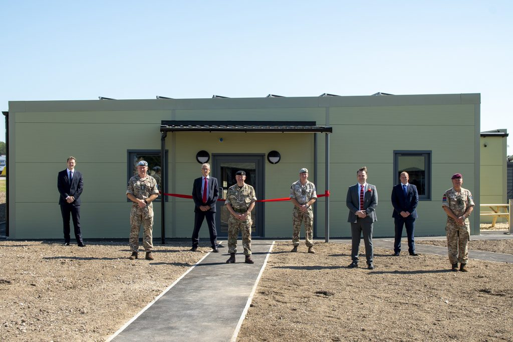 Eight men stand, socially distanced, outside a single storey green building. The foreground is bare earth, unlandscaped, with a path leading to the building. Four of the men are wearing military camouflage uniform, the others are dressed in dark suits.