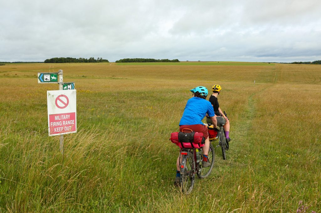 Two cyclists are crossing green land on the Salisbury Plain Training Area. One is wearing a black top with a yellow helmet, short and purple socks and there is another cyclist right behind him in a blue helmet, blue short sleeved top and red shorts with a small red bag on his bike. Next to them is a sign saying 'Military Firing Range Keep Out' and around them is a green field.