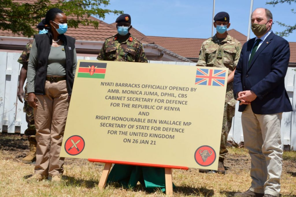 Ambassador Dr Monica Juma and Ben Wallace MP stand on either side of a large sign marking the opening of Nyati Barracks, with two uniformed Kenyan soldiers and one uniformed British soldier behind them.