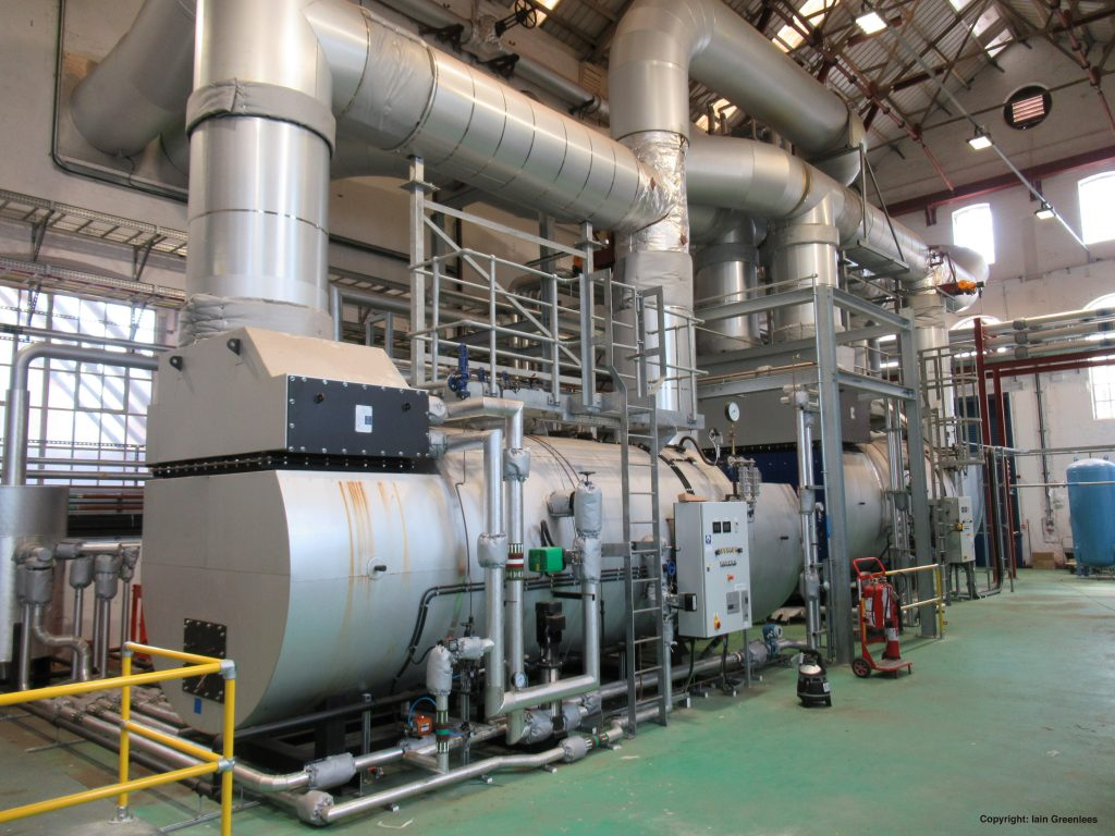 The Combined Heat and Power Plant boiler is silver and has green flooring underneath.