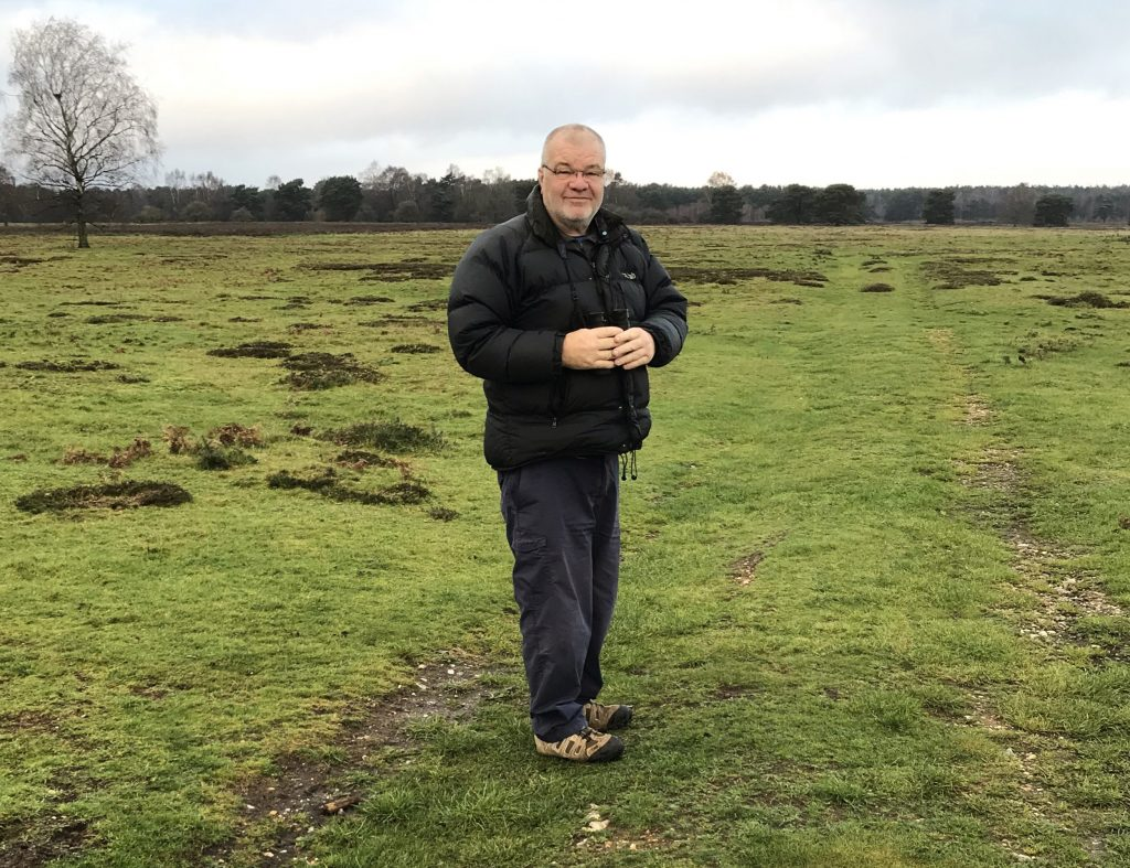 Peter is wearing a black puffed coat and black heans with brown trainers. He is wearing glasses and is standing on green heath at the Stanford Training Area. Behind him in the distance is a tree.