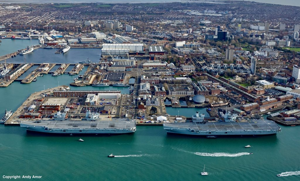 Both the Royal Navy's Queen Elizabeth Class aircraft Carriers pictured next to each other at the HMNB Portsmouth harbour. The water is a green/blue colour and there are buildings located behind the vessels.