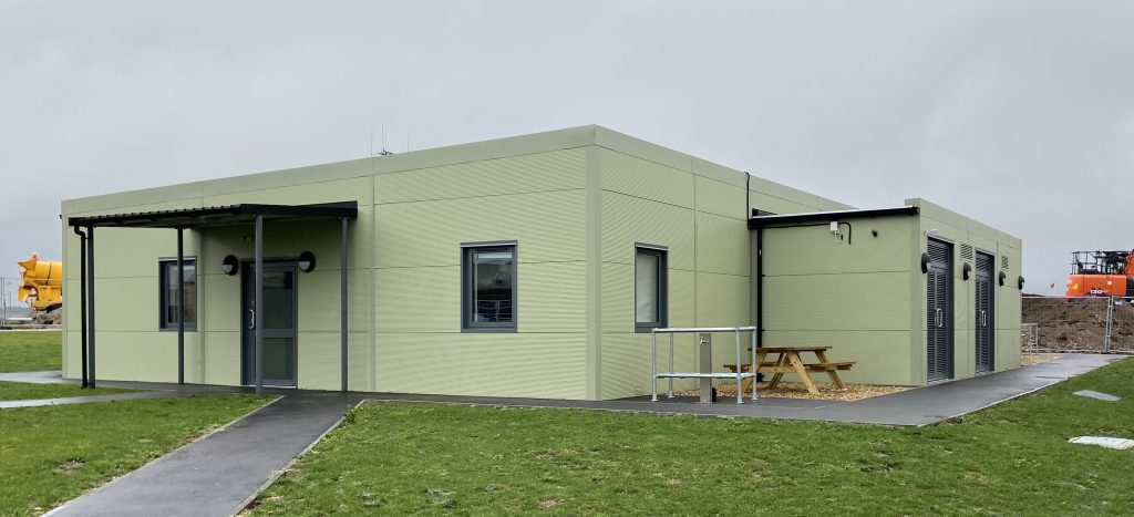 Light Green one floor modular building with two windows with grey boarding around it at the front and a dark green door. On the side is a wooden bench and around the building is grass. Located infront of the door is a grey path.
