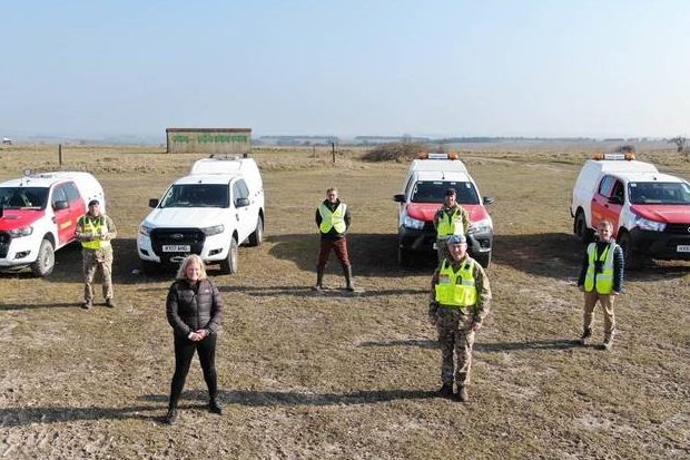 Lucy standing outside with members of the training estate team and four vehicles on an open plain. The image is taken from a drone so is from a little way in the air.