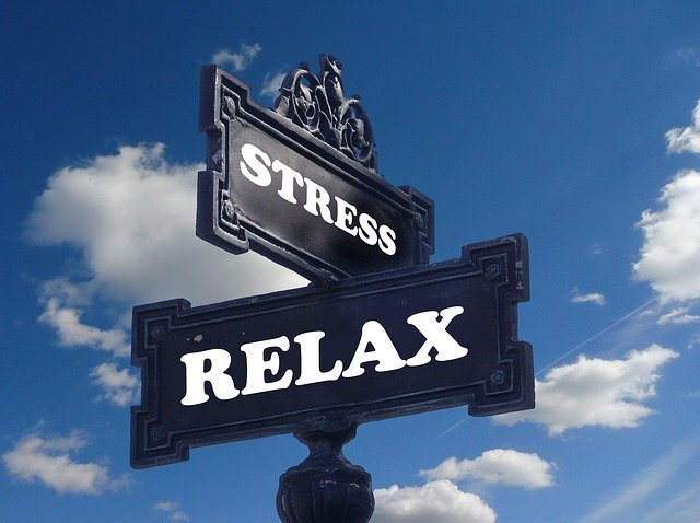 A black sign with white wording that say stress on it with another black sign under it that says relax in white text. There is sky and clouds behind the sign.
