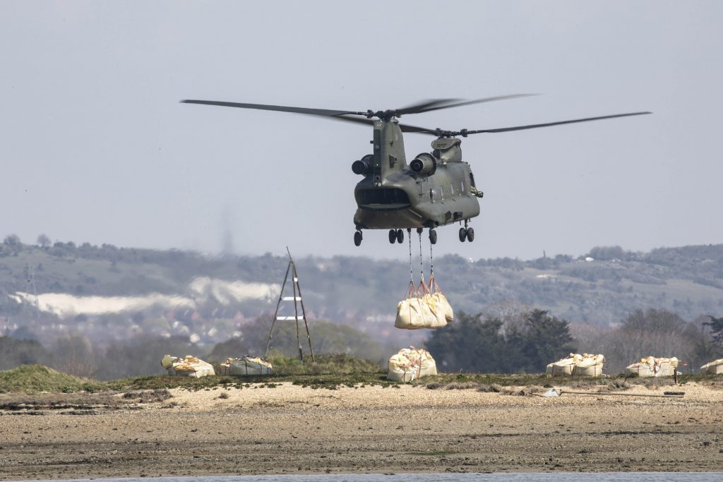 A Chinook lowers large bags of aggregate on to the island.