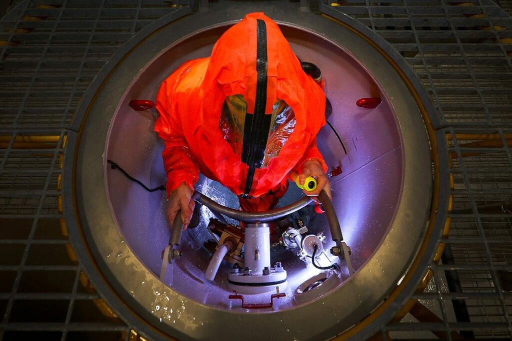 A submariner is climbing out of a training submarine hatch, he is wearing a hooded orange hi-vis full body outfit. The hatch is silver with a silver ladder in it.