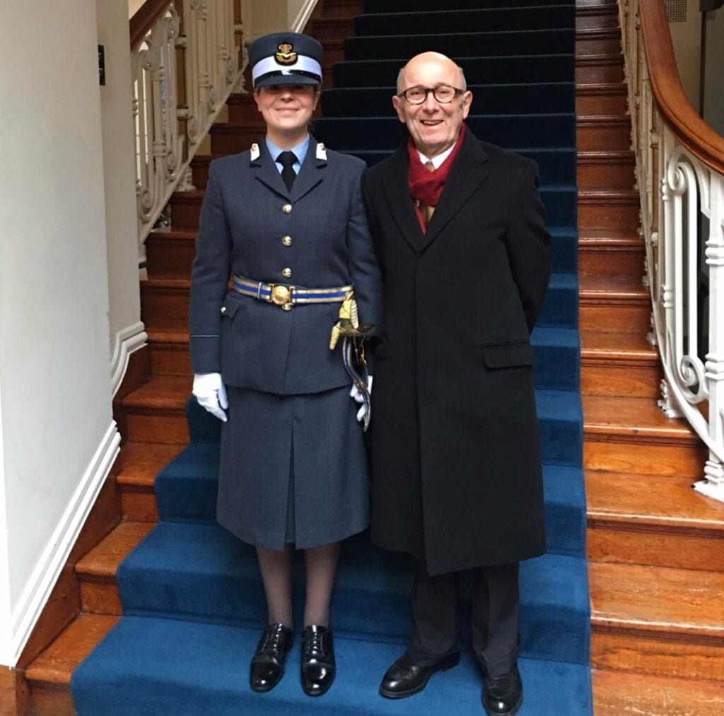 Annabel is standing on some stairs with a dark blue carpet wearing a long navy blazer jacket with three gold buttons and a gold and blue belt around it. She has a long navy skirt on and black shoes. She is also wearing a hat with the Royal Air Force symbol in circle in the middle. Next to her is her father in a long black coat, black shoes and black glasses.