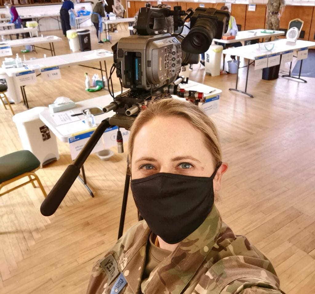 Annabel is wearing a long green Armed Forces top and is taking a selfie. She has a black mask on covering her mouth and blonde hair tied back. There is a camera behind her and seven white tables that are spread out.