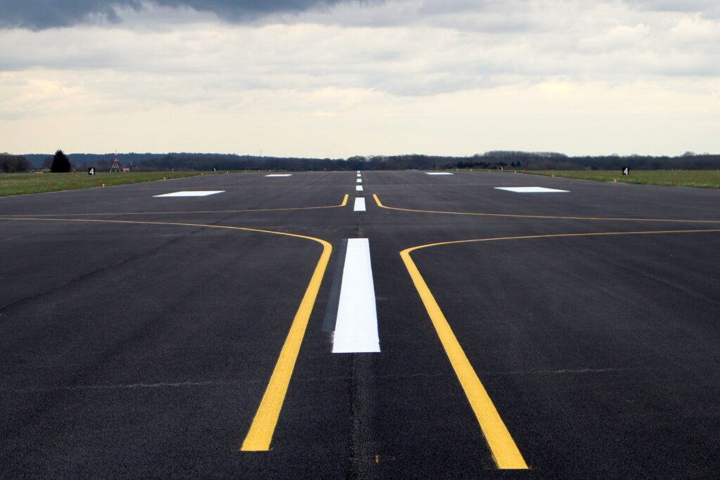 The foreground is the resurfaced runway. The surface is dark and has a dotted white line progressing up the middle with yellow lines arcing away to the each side.