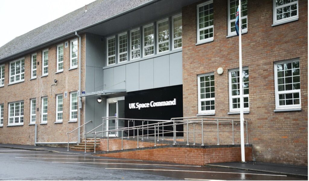 An external picture of the new UK Space Command HQ. It's a two story brick building with the words 'UK Space Command' written in white on a black background above the entrance.
