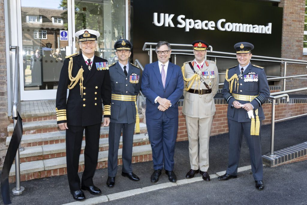 Five men standing outside the UK Space Command HQ. One is in a blue suit, one in naval uniform, two in RAF uniform and one in Army uniform.