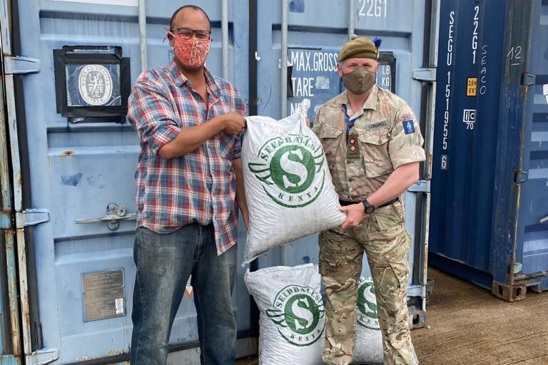 Two men stand in front of a couple of shipping containers. On the left is a black man, dressed casually, and on the right is a white man dressed in military uniform. Both are facing the camera and holding a sack of seedballs between them. Another sits on the ground between their legs.