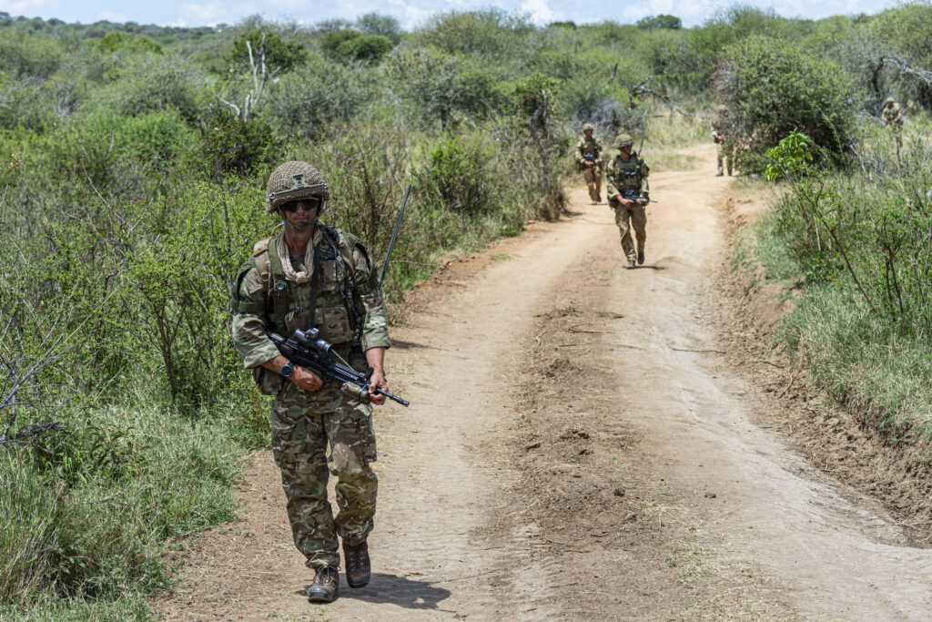 A dirt road with trees to either side takes up most of the foreground. It curves to the right. Three soldiers are visible, walking towards the camera.