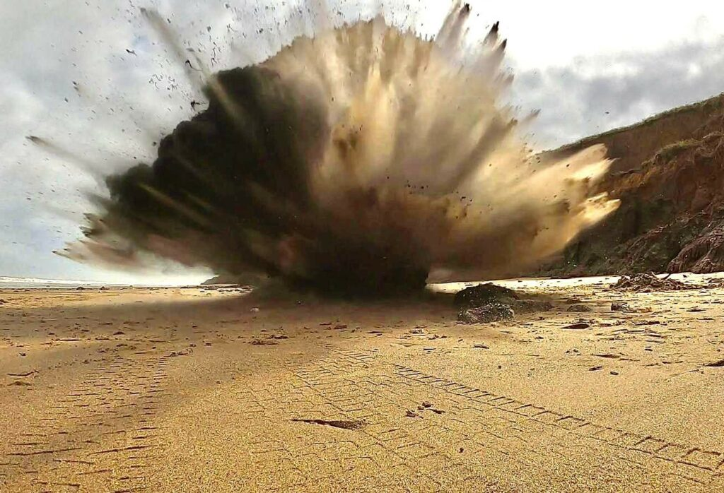 An explosion has sent sand blasting in all directions in the top of the image. The foreground is a sandy beach.