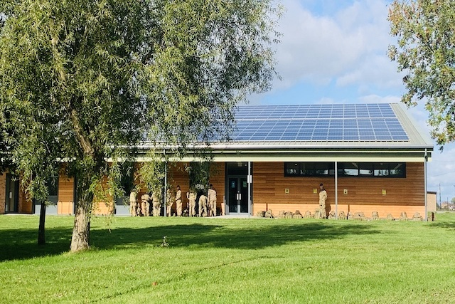 A rectangle light wooden building with solar panels across the roof. The door is black and there are windows at the right-hand side of the building. There are nine troops facing the building infront and a tree infront of the building with grass.
