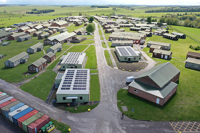 Aeriel view of the three new Net-Zero Carbon efficient buildings at Westdown Camp. The buildings are grey rectangle blocks with a flat roof and solar panels at the top. There is grass around them and a road. There are several other office blocks in brown around the buildings.